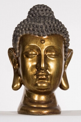 Statue head of Buddha, gold colour, peace and an atmosphere of serenity, resin